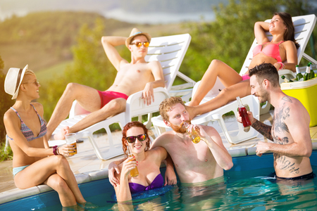 bathers: Young girl in hug with her boyfriend and friends drinking beverage on swimming pool at summer