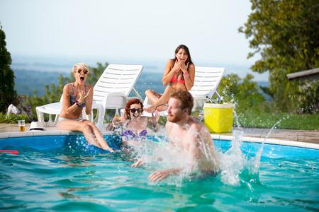 Guy éclaboussée femelles en bronzant quand sauté dans la piscine Banque d'images