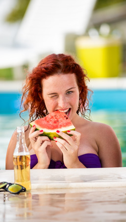 bather: Young ginger curly girl wink on piscine with slices of watermelon and drinks Stock Photo