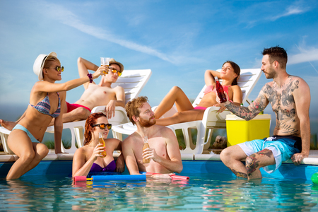 refreshes: Guys and girls refreshes on swimming pool with cold drinks at summer