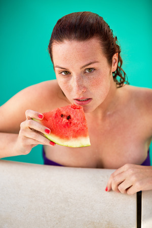 bather: Young ginger female spends hot summer day on swimming pool and refreshes with slice of watermelon Stock Photo