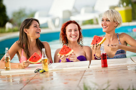 Three smiling girls enjoying at pool with slices of watermelon and drinks Stock Photo