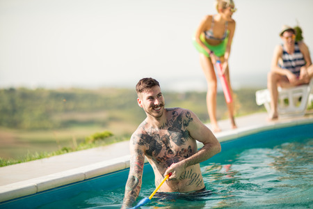 bather: Hipster tattooed guy have fun in open pool at summer