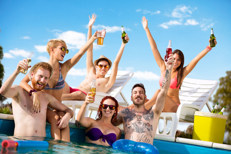 fun day: Young cheerful people having fun at summer in pool with refreshing drinks in arms