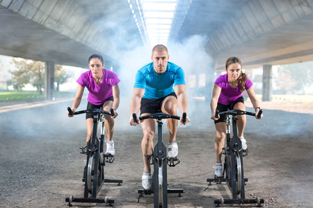 fitness training: young fitness people riding exercise bikes Stock Photo