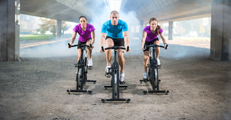 group of people doing spinning on cycle bike outdoor Stock Photo