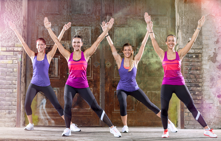 keep fit: Young group of woman in colorful athletic shirts keep fit shape exercising outdoor