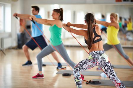 mujeres de espalda: Mujer con grupo de deportistas se expande goma resistente en el gimnasio