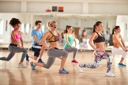 breech: Group of young people doing exercises for legs and breech in gym Stock Photo