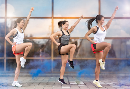 aerobic: Three athletic girls doing aerobic exercises outside