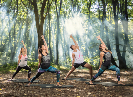 Group of young people perform easy stretching exercises in sun lighted forest