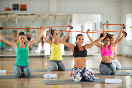 knell: Young female doing exercise in group with resistant rubber in gym Stock Photo