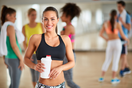 ponytail: Young sporty brunette with ponytail after training with bottle of beverage