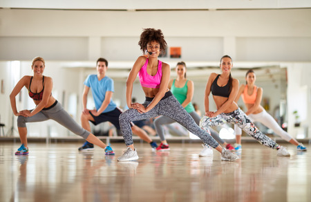 warming up: Warming up exercises with female instructor in course at gym