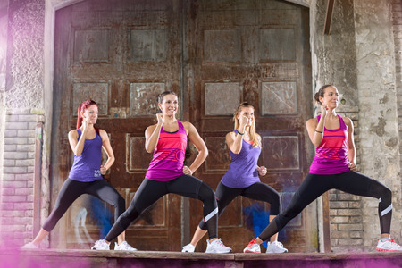 keep fit: Young female in colorful athletic shirts keep fit shape exercising outdoor