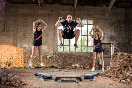 grit: Young sport people jump off on their grit condition training in hangar