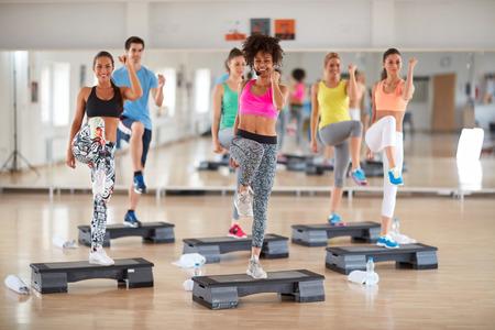 ejercicio aeróbico: Los deportistas en sportwears de colores con joven mujer instructor rizado en la formación del grupo