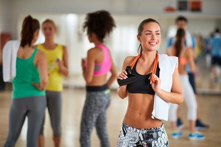 gimnasia aerobica: Brunette sonriente joven y delgada con aparatos de gimnasia para los brazos en el gimnasio Foto de archivo