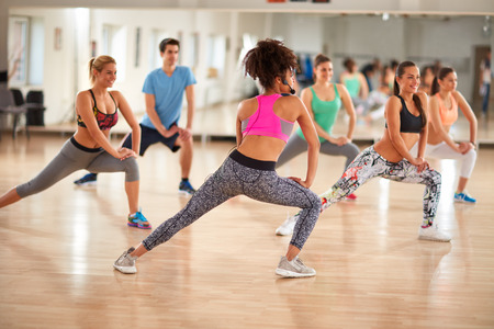 stretching condition: Young group of fitness exercisers in colorful sport clothes with female instructor in fitness class