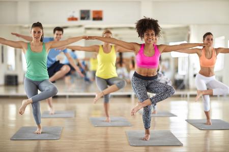 Grupo de gente joven del deporte tienen el entrenamiento del equilibrio del cuerpo en el gimnasio