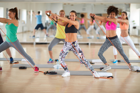 Las mujeres jóvenes usan goma resistente para los ejercicios en el gimnasio