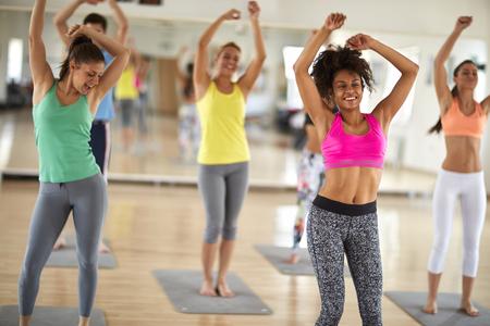 Aantrekkelijke vrolijke vrouwen dansen op sportschool in kleurrijke sportkleding Stockfoto