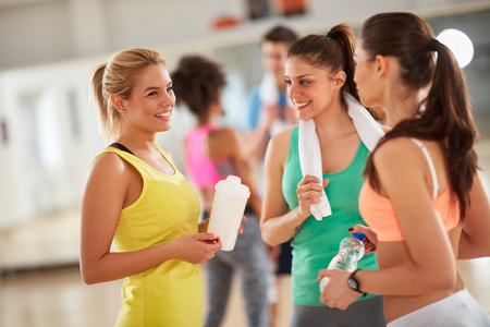 Smiling girls in group chatting after training in fitness center