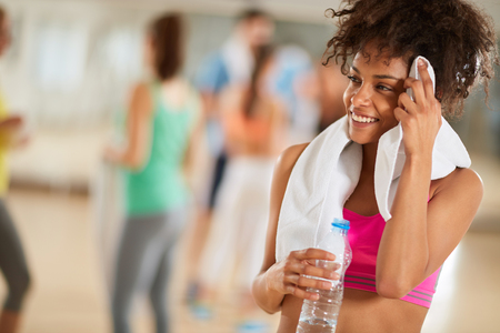 Fatigué et moite mais satisfait femme bâtarde après séance d'entraînement au gymnase