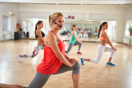 instructor: Young female fitness instructor with microphone training group in fitness class Stock Photo