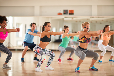 Fitness group doing exercises for shaping breech on fitness class Standard-Bild