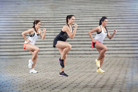 stretching condition: Group of young sportswomen doing aerobic exercises outdoor