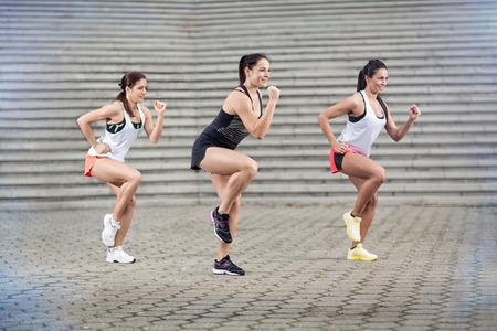 ejercicio aeróbico: Grupo de deportistas jóvenes haciendo ejercicios aeróbicos al aire libre Foto de archivo