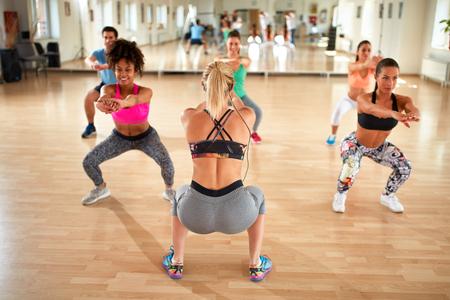 gimnasia aerobica: entrenador Hembra joven que hace ejercicio de sentadilla con el grupo de la aptitud