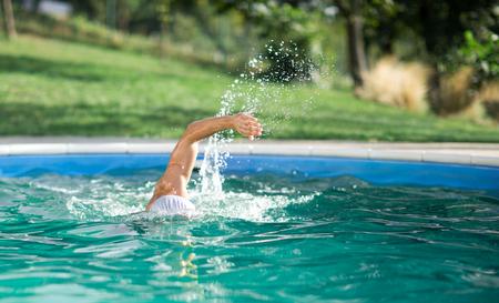 backstroke: swimmer recreating on outdoor pool