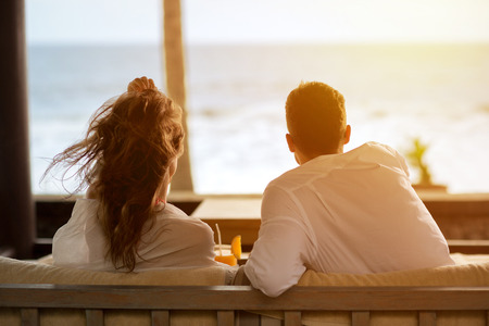 luxury apartment: couple watching the sea from the terrace of  their apartment, enjoying in beautiful view