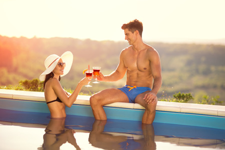 Couple in love toasting with cocktail in swimming pool, luxury vacation