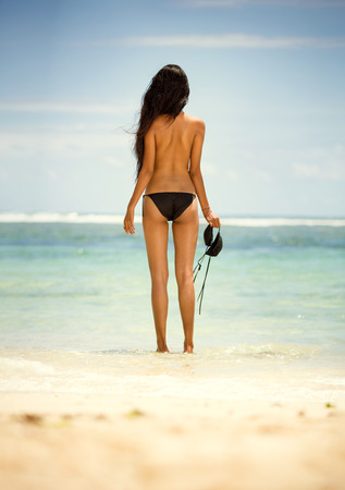 Back view of woman in topless, standing on beach Stock Photo