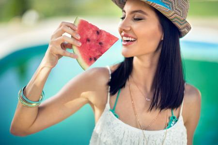 Junge Frau mit Sommerhut beißt saftige Wassermelone