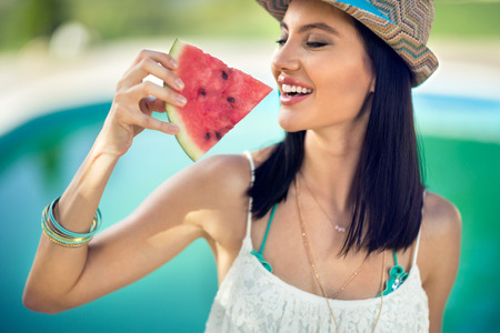 Young woman with summer hat bites juicy watermelon Stock Photo