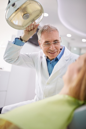 searchlight: Male dentist adjust searchlight to illumine patients mouth