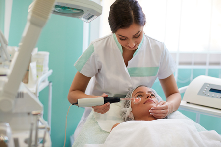 hydro: Young woman in cosmetic hat receiving darsonvalization facial treatment at beauty salon.