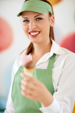 candy store: Young attractive woman employed in candy store with ice cream in cone Stock Photo