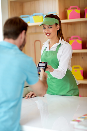 pay bill: Saleswoman and customer who pay bill with banking card in confectionery