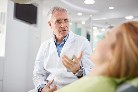 Mannelijke tandarts op werkplaats met vrouwelijke patiënt in tandheelkundige praktijk