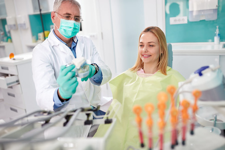 Dentist show to his female patient teeth model in jaw in dental clinic