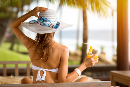 back view: back view of long haired woman in bikini and wearing a hat on tropical beach