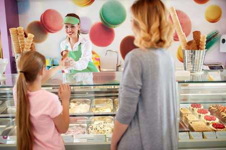 woman with ice cream: Female seller in bakery gives ice cream to girl