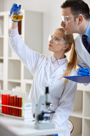 experimentation: students research experimentation in laboratory holding chemical flask