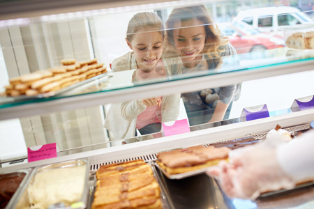 candy store: Daughter and her mother choose sweets in beautiful candy store