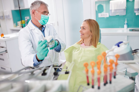 intervention: Male dentist discusses about upcoming intervention with female patient